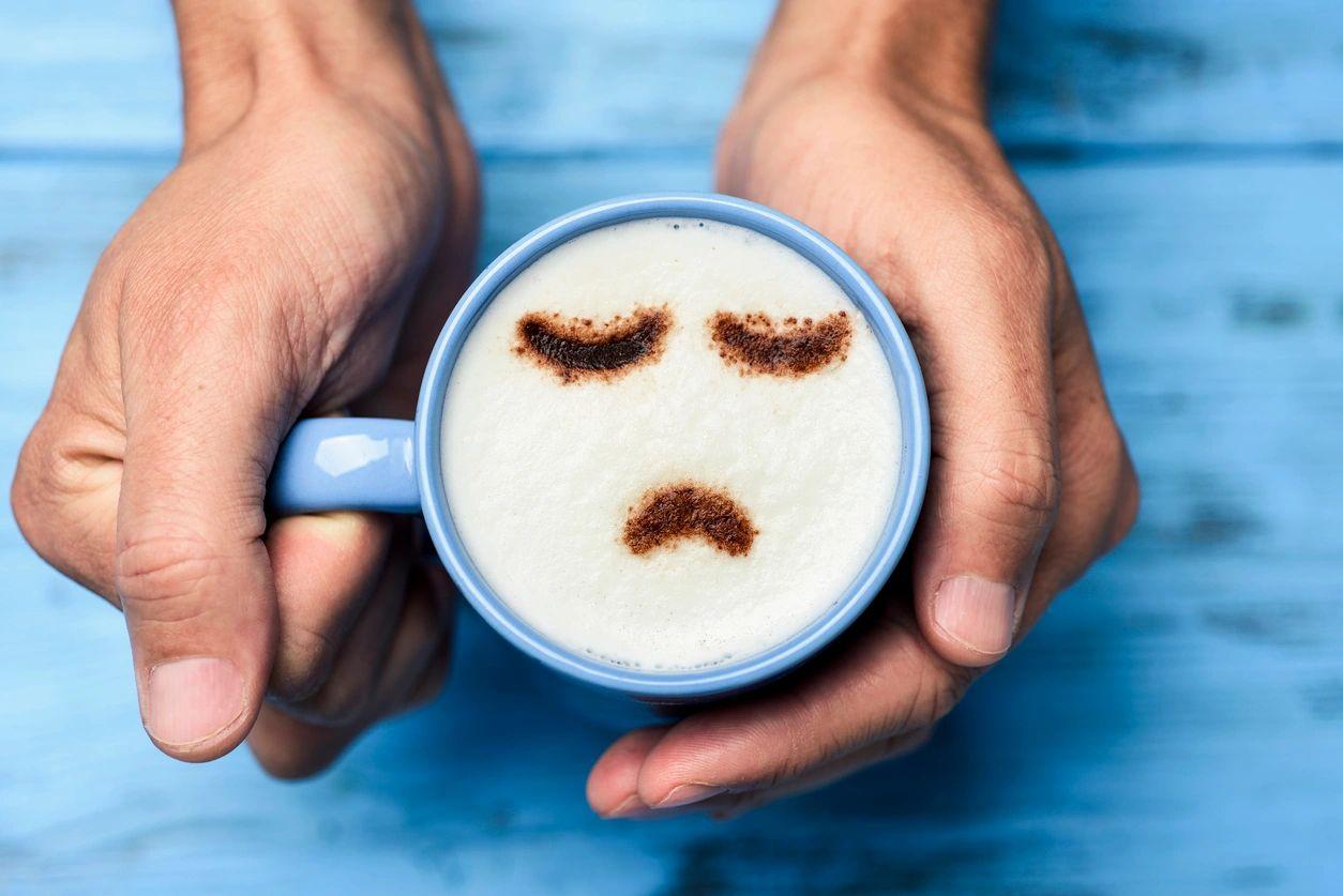Depression Sad face in a blue cup